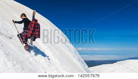 Young snowboarder stepping snow and climbing up to the mountain ridge by the steep