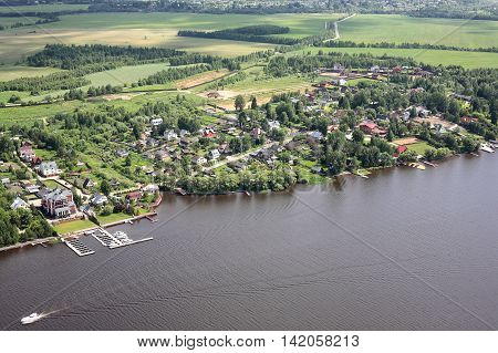 Aerial Views - Russia. Houses moorings and other constructions on the river bank Volga. Shooting from the helicopter.