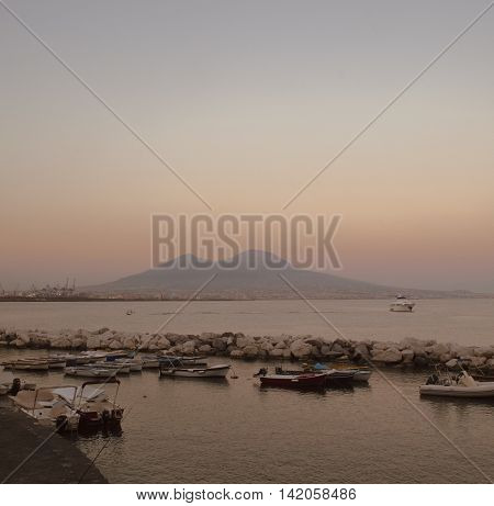 Harbour with boats in front of Mount Vesuvius in a summery sunset
