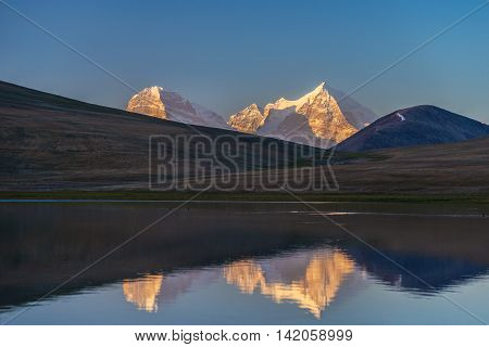Sunlit Karl Marks and Friedrich Engels peaks are reflected in Turumtaykul lake (Pamir Mountains). Blue sky in background.