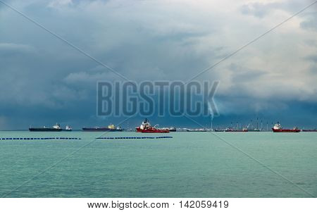 View of the Singapore Strait from Sentosa Island. Ships, industrial landscape and stormy weather.