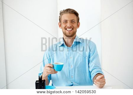 Close up portrait of young handsome cheerful smiling businessman standing at table holding cup of coffee. Looking in camera. White modern office background.