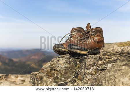 Winter sports style woman's Hiking boots on the rock. Natural leather and fur. Heavy-duty cold-resistant outsole