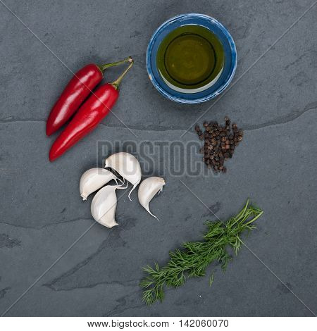 Dill red peppers black pepper corn oil and garlic on a grey slate plate stock picture