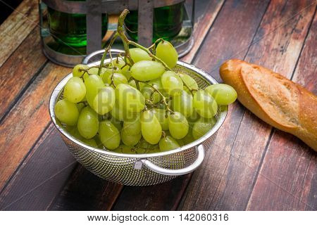 Fresh grapes in stainless steel colander on a wood surface