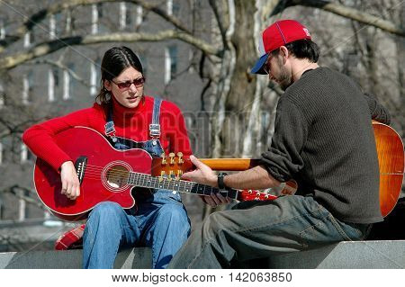 New York City - March 7 2006: Two musicians strumming their guitars on the wall in front of Grant's Tomb in Riverside Park