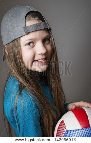 studio portrait of smiling girl in grey cap with ball in hands