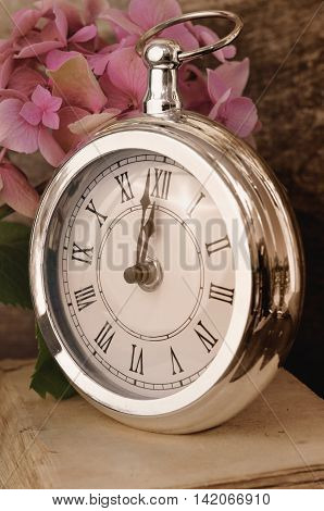retro clock at twelve on old book and hydrangea flower background
