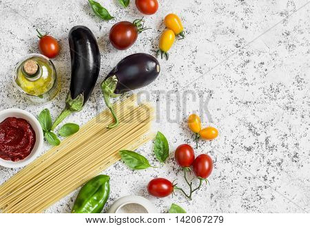 Raw ingredients for making pasta - spaghetti eggplant tomatoes pepper olive oil tomato sauce and basil . Cooking background top view