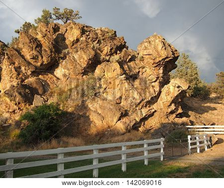 Large Rocks on a farm in Central Oregon in the western United States are lit up with a beautiful gold color due to the light of an evening summer storm.