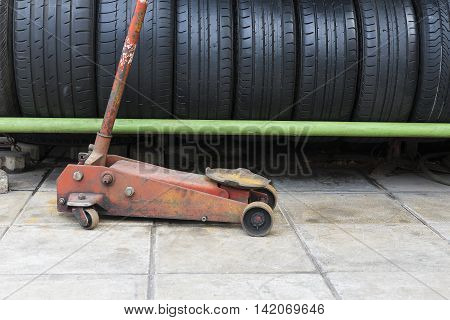 The old floor jack with the car used tire stack background.