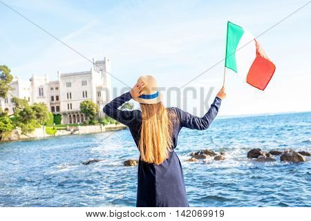 Young female traveler with italian flag near Miramare castle in northeastern Italy