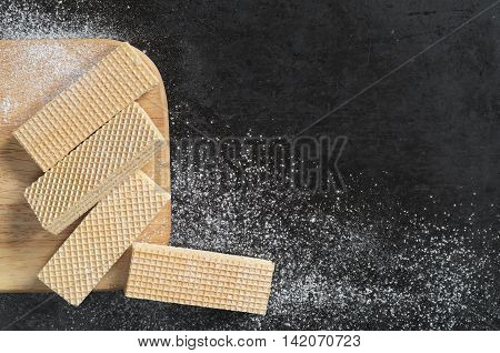 Wafers on kitchen board on a black metal background top view