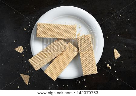 Sweet wafers in white plate on black metal background top view