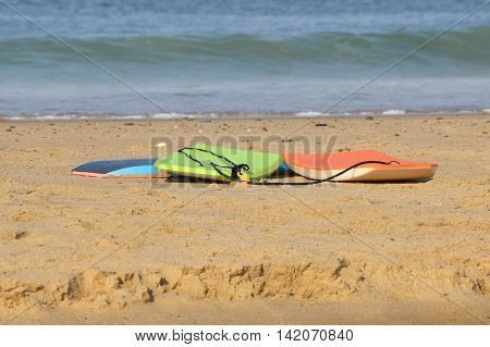 Three boogie boards lying on the sand on a sunny day the beach.