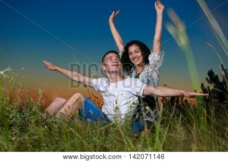young romantic couple open arms and having fun at sunset on outdoor, beautiful landscape and dark sky, love tenderness concept, young adult people