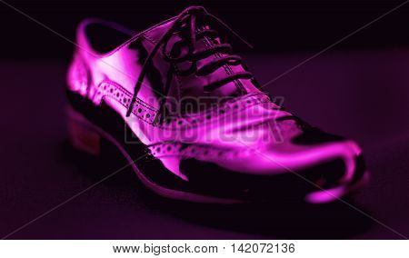 Footwear Concept. Horizontal Image. Pair of black female classic leather shoes on the black background. Selective focus. Pink colored.