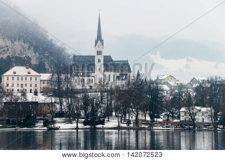 Bled lake in the morning Slovenia. Fog over the city. Famous church in the mountains