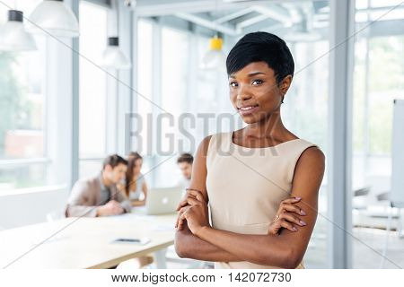Successful african american young businesswoman standing with hands folded in office