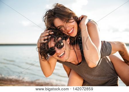 Young smiling man giving piggyback ride to girlfriend by the ocean