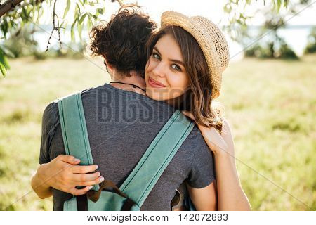 Two young hipster lovers hugging in the forest