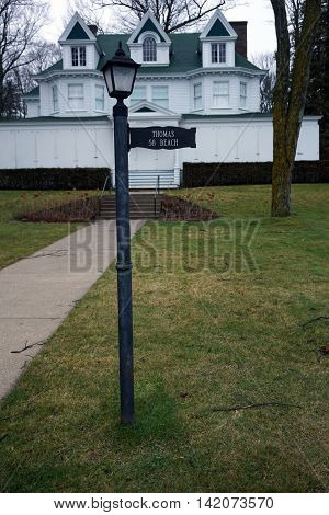 WEQUETONSING, MICHIGAN / UNITED STATES - DECEMBER 22, 2015: A lamppost, with an attached sign indicating the house number and owner's name, stands in front of a large white home, christened Cedarmere, on Beach Road in Wequetonsing.