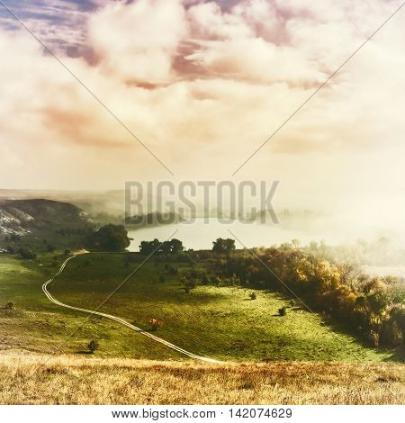 Vintage landscape with sky and fog over lake