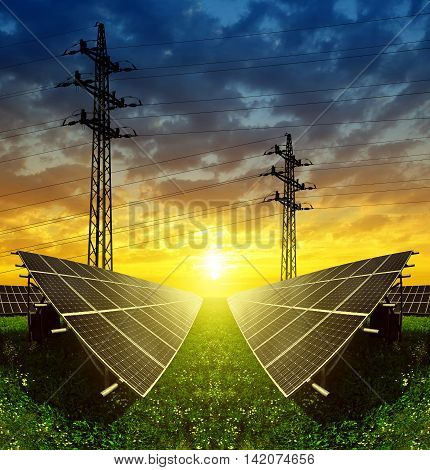 Solar panels with electricity pylon at sunset. Concept of sustainable resources.