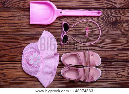 Summer accessories of kids on wooden background