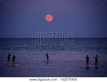 BARCELONA/SPAIN - 20 JUNE 2016: Standup paddleboarding under the strawberry moon at Barceloneta beach