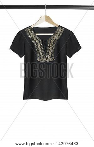 Black ethnic t-shirt on wooden clothes rack isolated over white