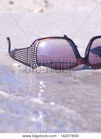 fashinable sunglasses on the sand