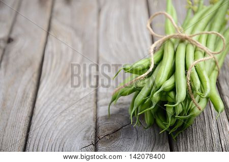 French beans on wooden background, selective focus, copy space