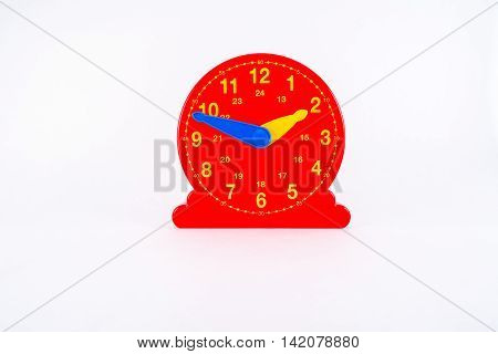 Educational red plastic clock toy with two hands and hours painted in yellow for learning time.