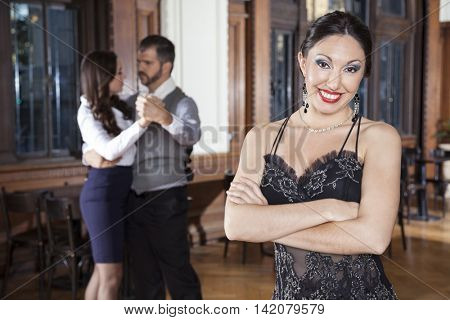 Confident Woman Standing Arms Crossed While Dancers Doing Tango