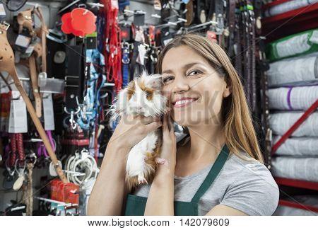 Beautiful Saleswoman Holding Cute Guinea Pig At Store