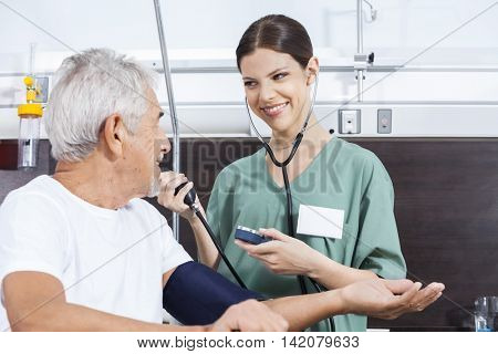 Nurse Checking Blood Pressure Of Male Patient In Rehab Center