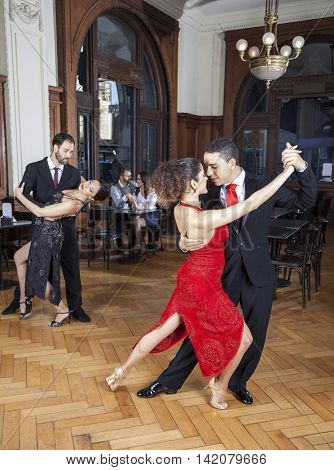 Passionate Dancers Performing Tango While Couple Dating In Resta