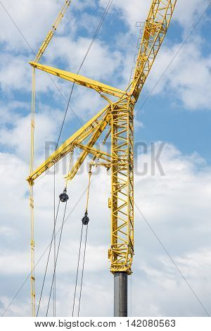 Large yellow telescopic crane against a cloudy sky