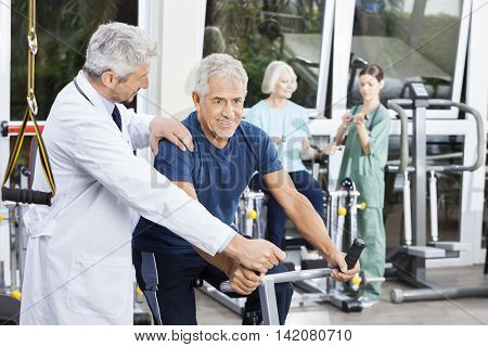 Doctor Instructing Senior Man On Exercise Bike At Fitness Center