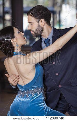 Passionate Dancers Performing Tango In Restaurant