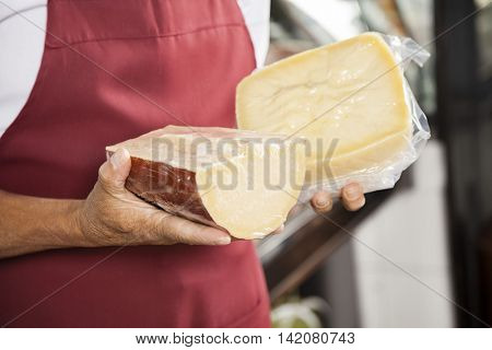 Salesman Holding Packed Cheese Pieces In Shop