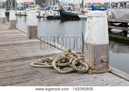Wooden pier with bollard and rope in harbor Urk The Netherlands