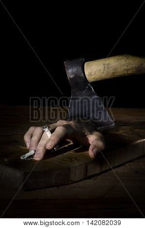 Man's hand with a cigarette chopped off with an ax.
