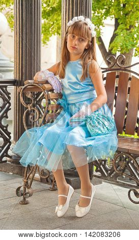 cute little girl in beautiful blue dress with bag in her hands sitting on bench