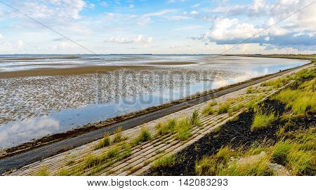 Bended embankment next to a Dutch estuary at low tide on an early morning in the summer season.