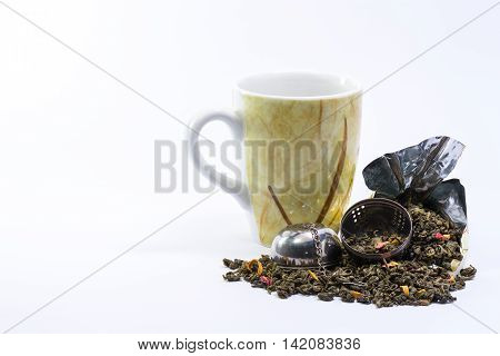 A nice Mug and an open infuser with mango green tea on a white background