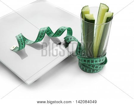 Bathroom scale with sliced cucumber on white background