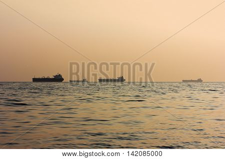 silhouettes of cargo ships at sea at sunset selective focus