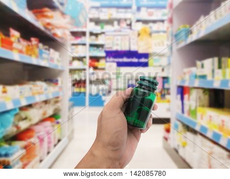Hand with plastic pill bottle on blurred pharmacy store background